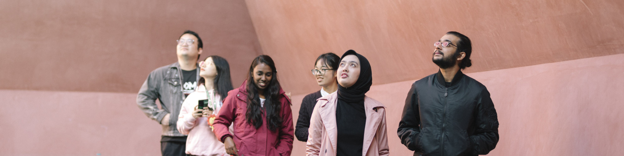 A group of students stand against a pink background looking up to the sky