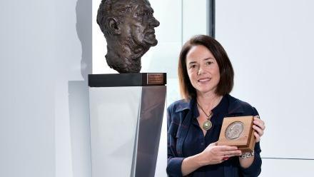 Professor Carola Vinuesa, with a bust of Howard Florey, at The John Curtin School of Medical Research. Image Stuart Hay, ANU