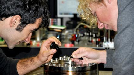 PhD students Giovanni Guccione (L) and Harry Slatyer examine their gold-coated silver gallium nanowire in the Quantum Optics labs.