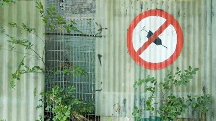 "Picture of fence with a ""no shooting up with syringe"" sign on it"