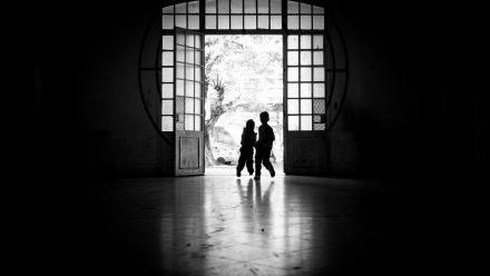 Photo of children walking through silhouetted door