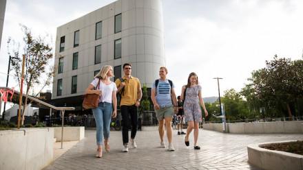 four young people walk together down a path