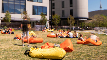 people relax on yellow and orange bean bags on a lawn in front of buildings