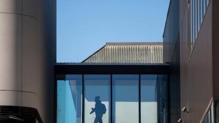 photo of person behind window walking between two buildings