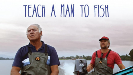 Film poster of the documentary: Teach a man to fish. There are two men on a boat making their way through a lake