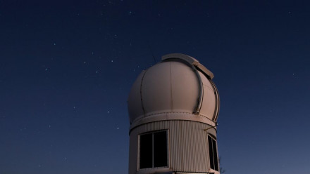 Image of a telescope and the open sky full of stars