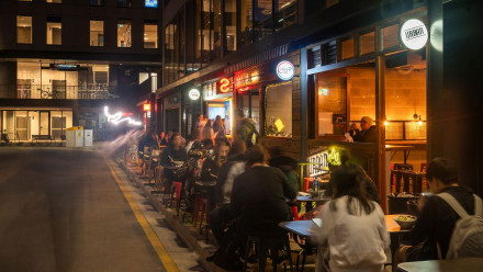 people eating at restaurants in a laneway at night