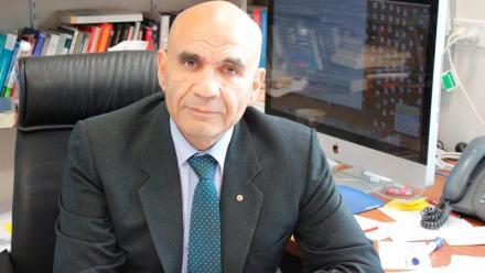 Portrait of Professor Amin Saikal sitting at his desk