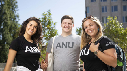 Three ANU students smile to camera