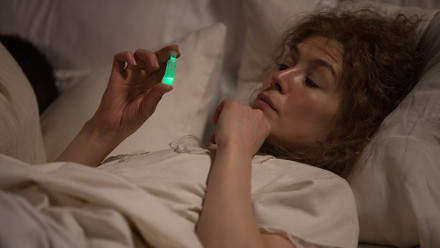 Marie Curie holding a tiny vial filled with luminescent green substance