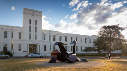 Pictured is the front of ANU School of Art which features a white building and sculpture