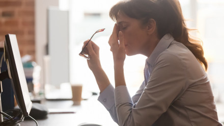 Stressed lady at desk in front of her computer pinching her nose bridge with her reading glasses in her hand.