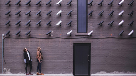 Exterior wall with about 30 surveillance cameras mounted on it. All cameras are pointing to two women at the base of the wall