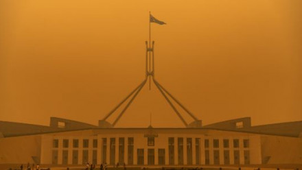 A dense orange haze of bushfire smoke covers Australian Parliament House during the 2019-20 Black Summer Bushfires.