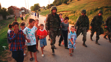 American Marines march with local children down street of Zegra, Kosovo