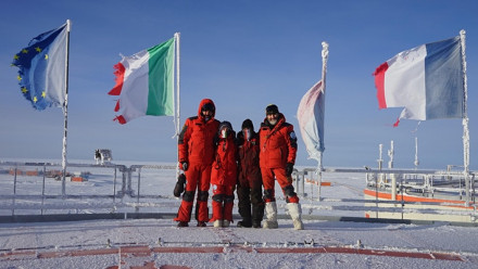 A team of four people in Antarctica, dressed in red thermal gear, standing together smiling and looking at the camera, with the French, Italian, and European Union flags behind.