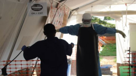 Person in mask, gown, and gloves being washed down with disinfectant in an ebola patient facility