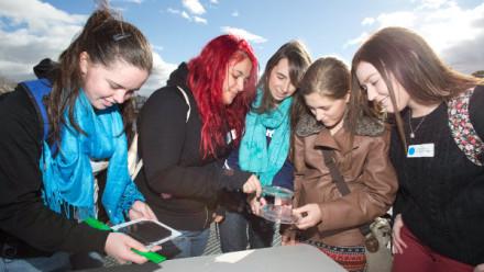 Five high school girls inspect solar cells
