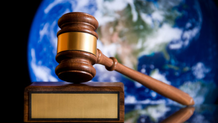 Image of gavel with an image of earth behind it