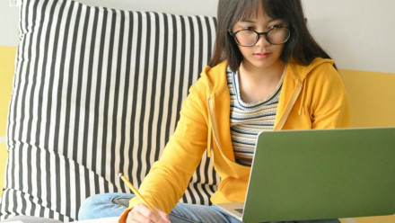 Person sitting on couch writing notes with laptop open.
