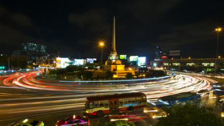 Photograph of a roundabout taken in timelapse where the cars look blurry because of their motion
