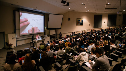 A darkened lecture hall filled with students taking notes. At the front of the lecture hall, an overhead projector displays a camera feed of the lecturer's handwriting.