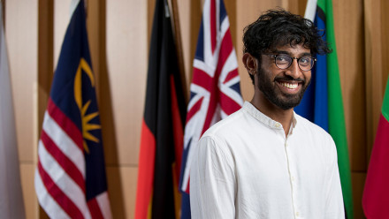 A male ANU student standing between the flags at the Hedley Bull Building