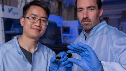 Researchers Dr Jun Pen and Dr Thomas White in the lab holding a solar cell