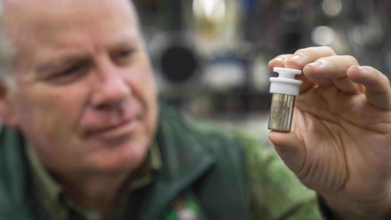 Professor Trevor Ireland from the ANU Research School of Earth Sciences holds a vial containing Moon dust collected by Apollo 11 astronaut Neil Armstrong during his first walk on the Moon. Image credit: Lannon Harley, ANU