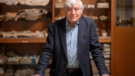 Photo of Emeritus Professor Peter Bellwood standing behind a desk.