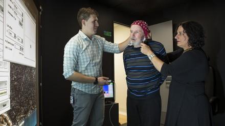 Researchers Alex Smith (L) and Dr Deborah Anthrop (R) work with Parkinson's disease sufferer Ken Hood. Image: Stuart Hay, ANU.