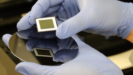 A close up image of a bifacial solar cell held by a person wearing blue gloves.