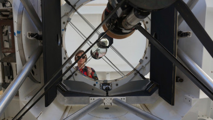 In this picture ANU instrument scientist Celine d'Orgeville stands in front of the EOS 1.8 meter telescope at Mount Stromlo Observatory where her image is reflected an infinite amount of times by the two telescope mirrors.