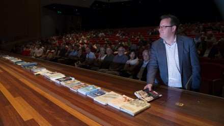 Book tribute - Dr Brendan Taylor, Head, Strategic and Defence Studies Centre, lays one of Professor Des Ball's books on the stage of Llewellyn Hall.