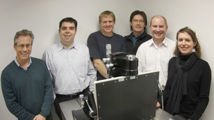 Mr Tim Sawkins, Dr Victor Pantano, Associate Professor Adrian Sheppard, Dr Trond Varslot, Professor Tim Senden, Dr Anna Carnerup standing in front of the first computed tomography system sold by ANU to Lithicon.