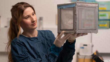 Hayley McNamara holding a box with mosquitos inside