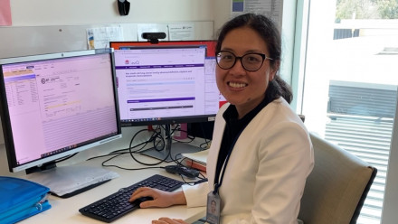 Dr Yada Kanjanapan sits at her desk in a white lab coat.