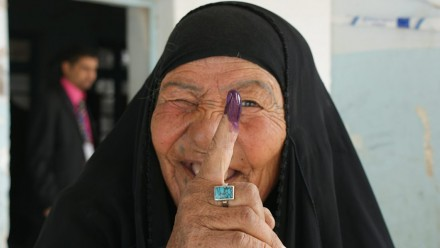An Iraqi woman displays her purple finger after casting a ballot during the 2010 Iraq election. Photo by DVIDSHUB on flickr.