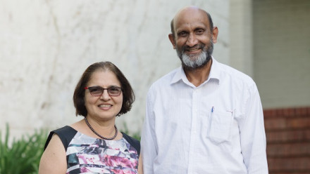 Vidya Jagadish and her husband Professor Chennupati Jagadish stnad smiling side by side in front of a building