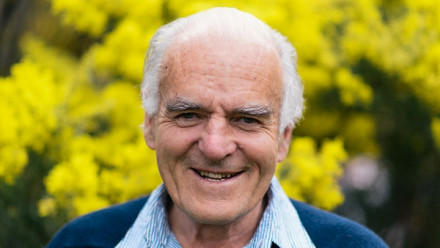 Professor John Love pictured smiling in front of yellow wattle bush at ANU campus on a beautiful warm day