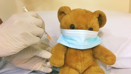 Doctor pretends to give a vaccination to a teddy bear