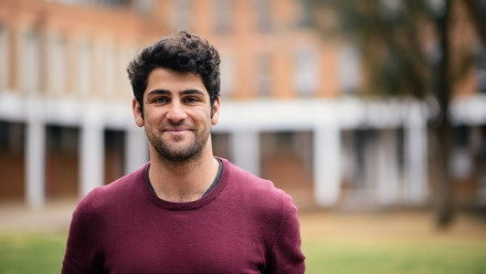 Nawaaz Khalfan stands smiling on the lawns of the ANU campus