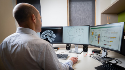 Picture of ANU Professor Nicolas Cherbuin sitting at his desk looking at a brain scan on his computer
