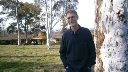 The late Dr Rob Lessile stands smiling and leaning on a large Australian gum tree