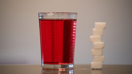 A red cordial drink next to sugar cubes