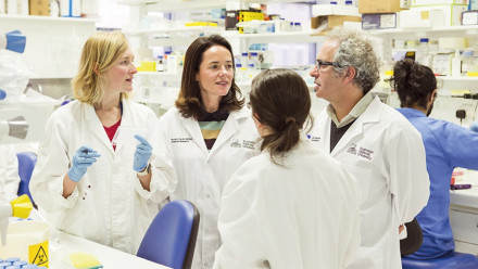 Group of people in lab coats. Professor Matthew Cook, far right