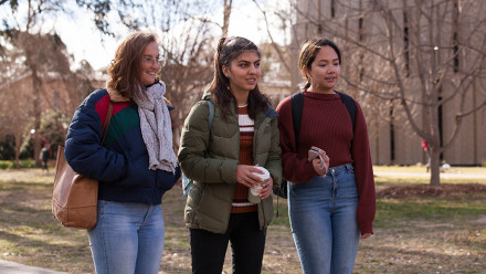 Sonesh and two friends walking on campus in 2019