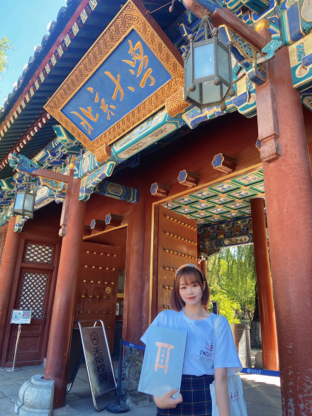 Anges GUO in front of the Landmark gate of PKU