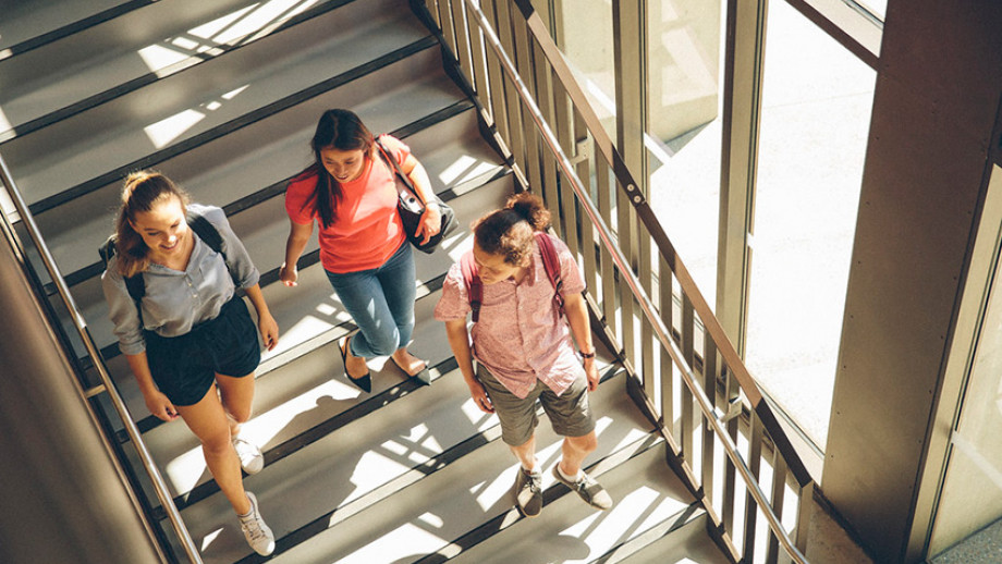 Three ANU students walking down the stairs