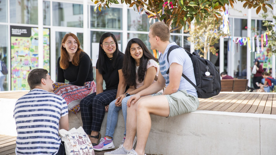 Five young students sitting and chatting on a bench outdoors